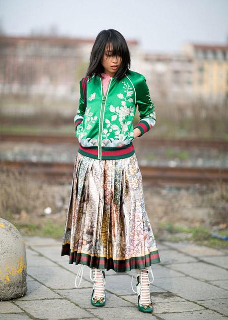 Модель в длинной плиссированой юбке и зеленой кофте с принтом