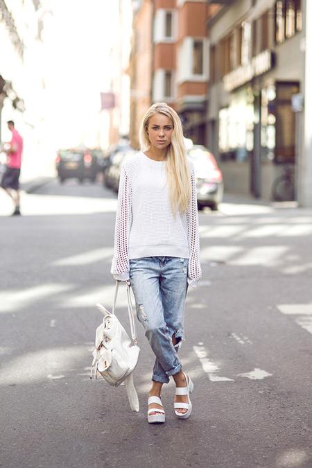 Модель в джинсах бойфренда, белая кофта, рюкзак и сандалии