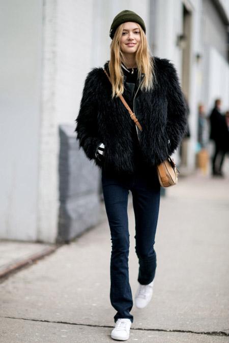 Модель в джинсах клеш, белых кроссовках, шапочка и меховая куртка