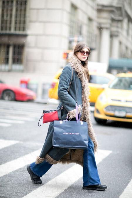 Модель в джинсах клеш и пальто с меховой отделкой