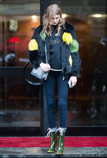 Модель в джинсах скинни, свиншот и черная меховая куртка с зелеными и желтыми вставками