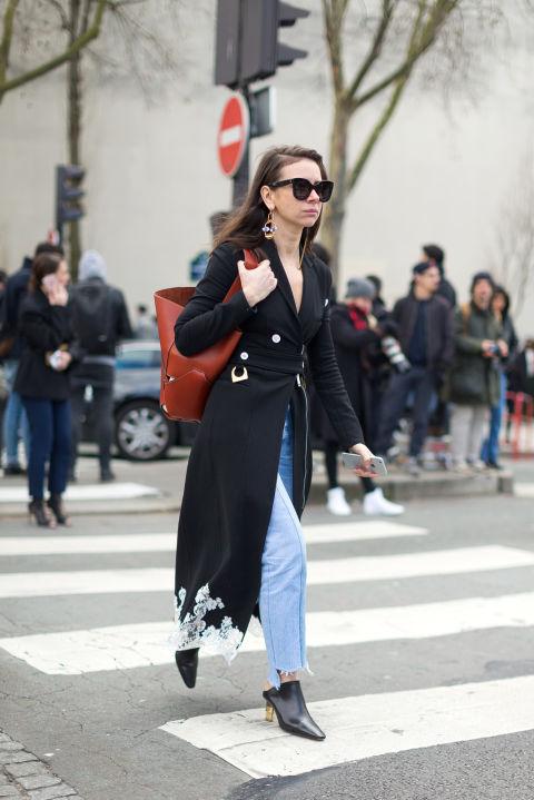 Модель в голубых джинсах, черном плаще и коричневая объемная сумка