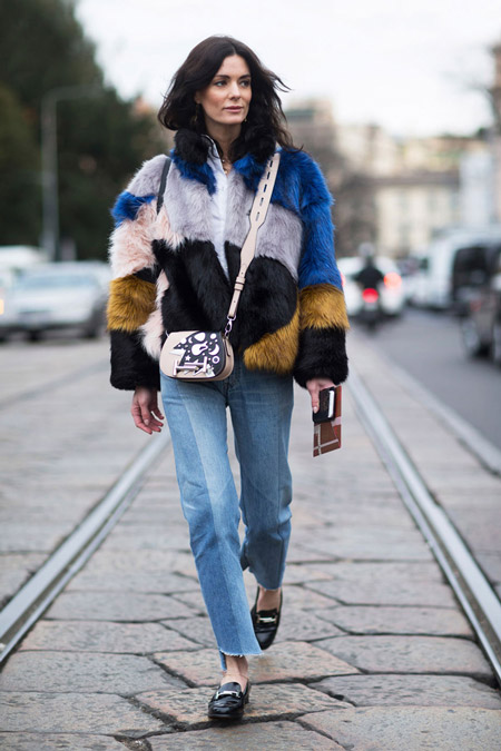 Модель в голубых джинсах и разноцветной укороченной шубке