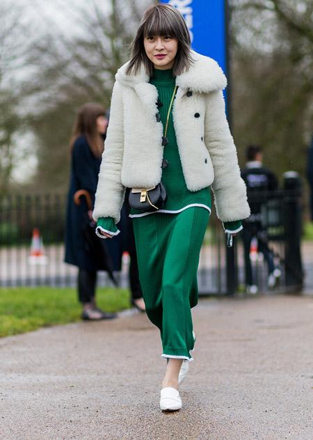 Модель в изумрудной юбке, кофта и белая шубка, маленькая черная сумочка, неделя моды - Лондон осень/зима 2016-2017