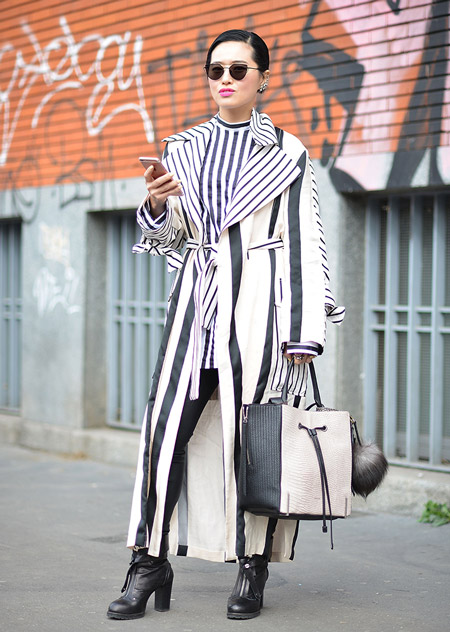 Модель в кожаных лосинах, черно-белый плащ в вертикальную полоску