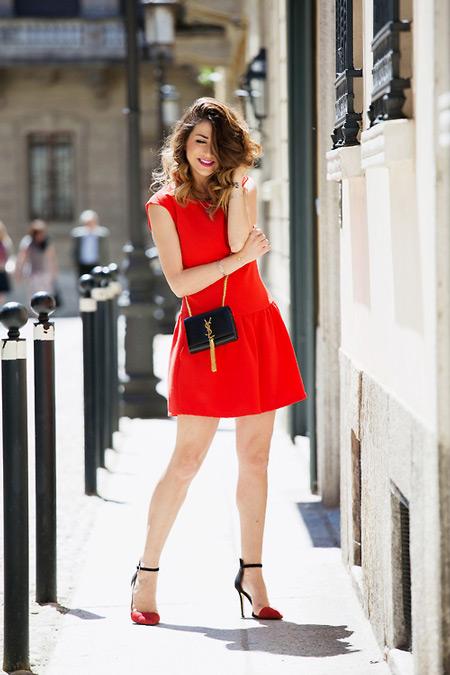 Модель в красном коротком платье, туфли на шпильке и черная сумочка