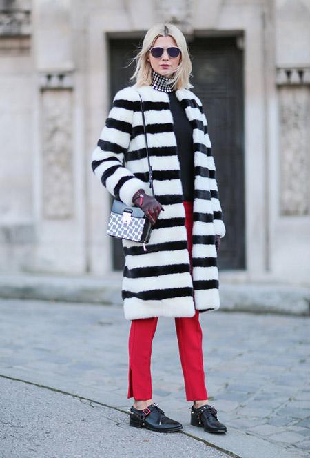 Модель в красных брюках, чернро-белая шуба в полоскку и маленькая сумочка