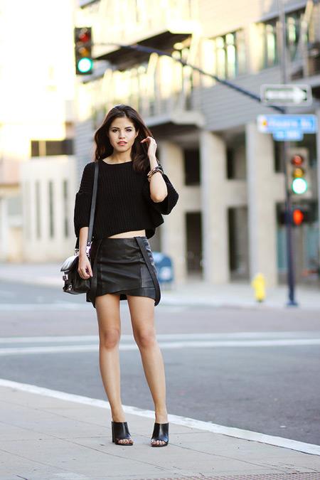 Модель в мини юбке, черный свиншот и черные босоножки и сумочка