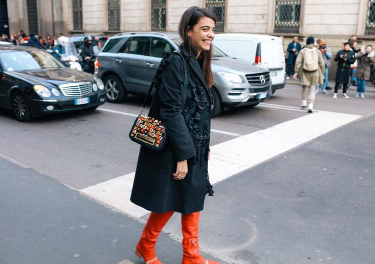Модель в оранжевых сапогах, черном плаще и разноцветная маленькая сумочка