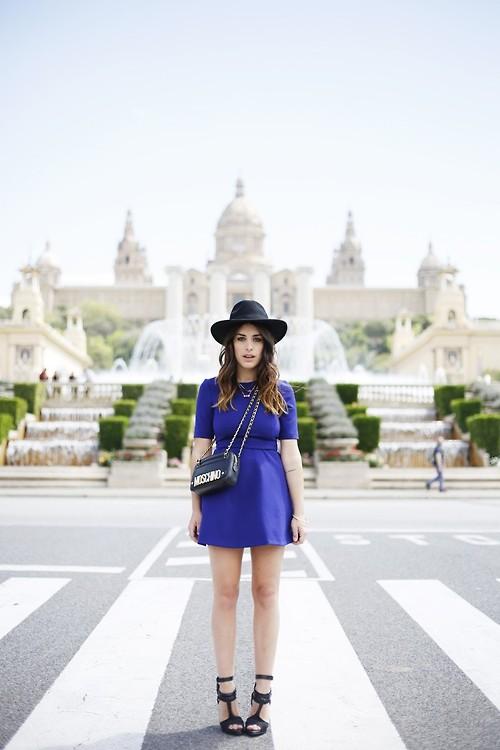 Модель в платье василькового цвета, черная шляпа, сумочка и босоножки