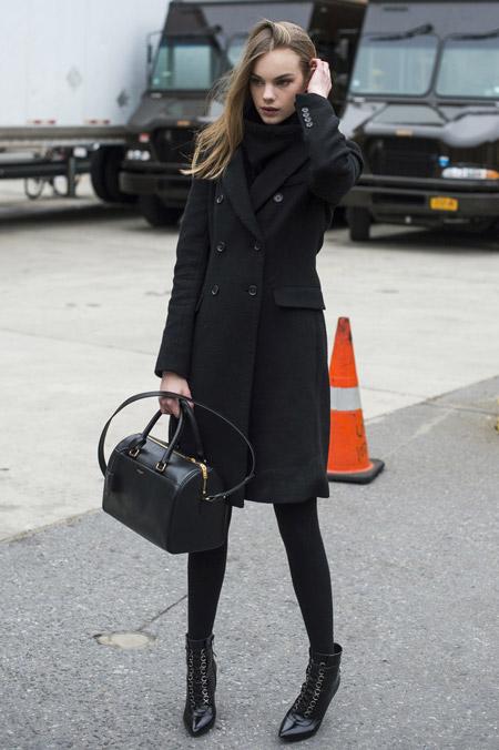 Модель в плотных колготках, ботильонах и черное пальто, объемная сумка