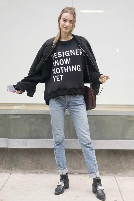 Модель в прямых джинсах, черный свиншот с надписями и куртка