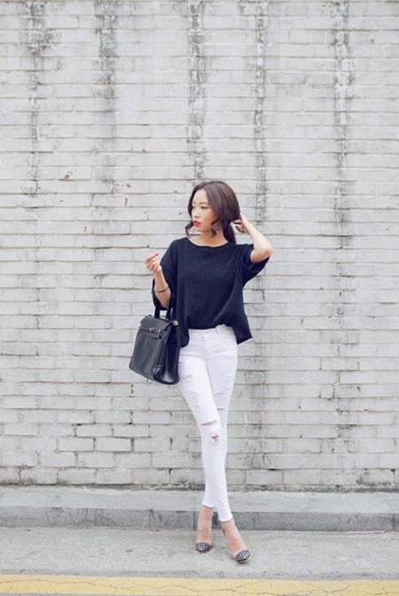 Модель в рваных джегинсах, черный свиншот, объемная сумка