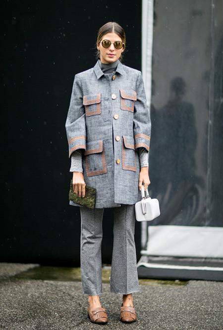 Модель в сером брючном костюме с удлиненным кардиганом и маленькая белая сумочка