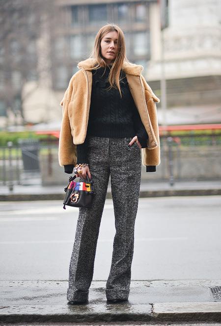 Модель в серых брюках со стрелками, черном свитере и бежевой куртке