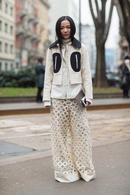 Модель в широких белых брюках, белой куртке с черными вставками