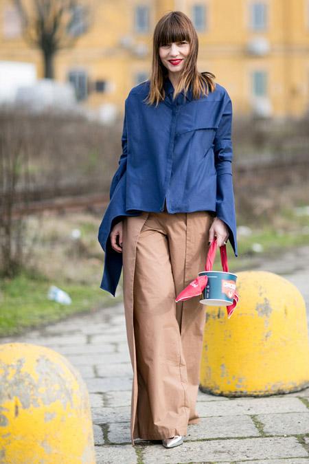 Модель в широких брюках песочного цвета и синей ветровке