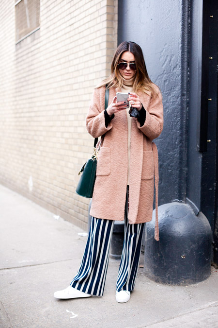 Модель в широких брюках в черно-белую полоску и нежно розовое пальто с накладными карманами