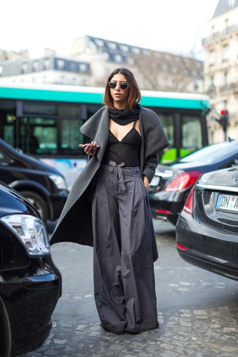 Модель в широкиз брюках, черный топ, шарф и серое пальто
