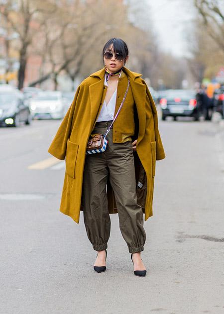 Модель в штанах, белой блузке и желтое пальто