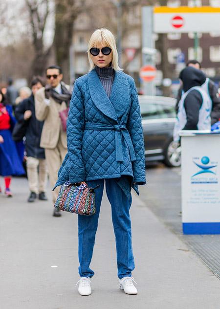 Модель в синих брюках, куртке и серая водолазка