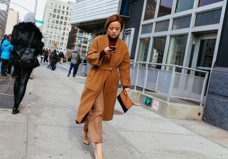 Модель в укороченных брюках и бежевом пальто, маленький клатч