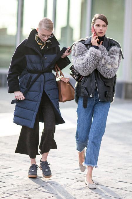 Модель в укороченных джинсах и кожанной куртке с меховыми рукавами