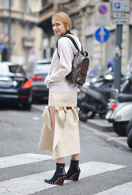 Модель в юбке оригинального покроя и куртке молочного цвета, рюкзак