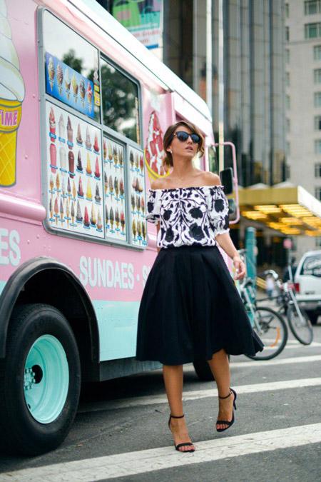 Девушка в блузке с открытыми плечами и юбке миди