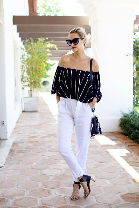 Девушка в черной блузке и белых брюках