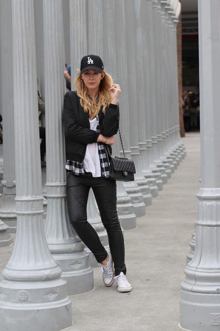 Девушка в черных брюках, белая футболка, черная куртка, кроссовки и кепка