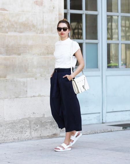 Девушка в черных широких капри, белая футболка, сандалии и сумочка
