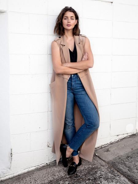 Девушка в джинсах, черный топ и бежевый длинный кардиган без рукавов