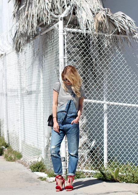 Девушка в джинсовом комбинезоне, полосатой футболке и красные босоножки