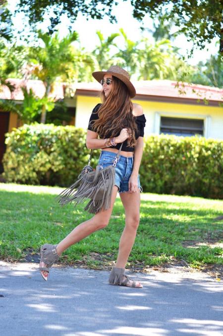 Девушка в джинсовых шорта, черный кроп топ, сандалии и шляпа