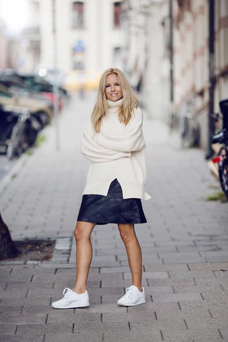 Девушка в кожаной юбке, белый свитер и кроссовки