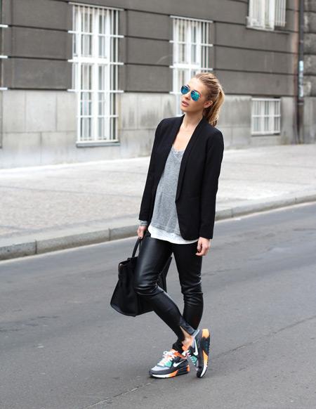 Девушка в кожаных брюках, серая футболка, черный жакет и кроссовки