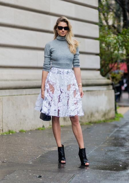 Девушка в прозрачной белой юбке, серой водолазке, черные ботильоны с открытым носком