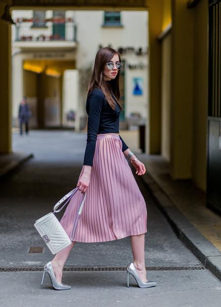 Девушка в розовой плиссированной юбке, черная водолазка,туфли на каблуке и белая сумочка