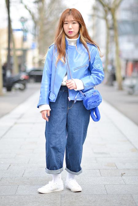 Девушка в широких джинсах, голубой кожаной куртке, белые кроссовки и водолазка