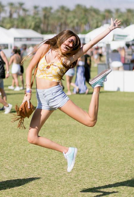 Девушка в шортах кедах и желтом топе - Коачелла 2016