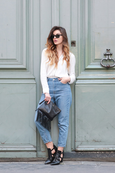 Девушка в синих джинсах, белая блузка и черные туфли и клатч с бахромой