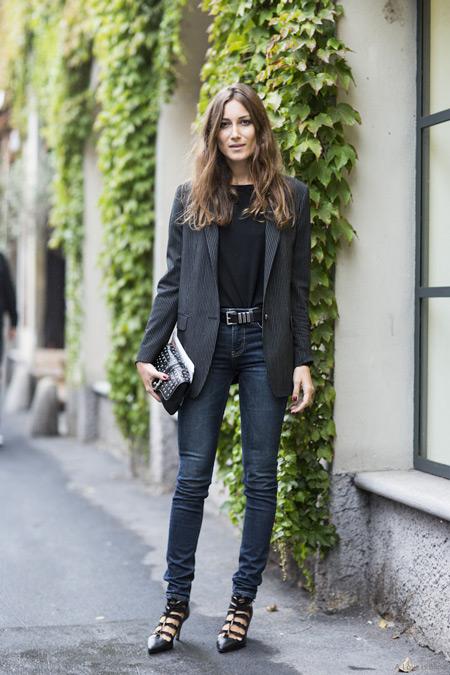 Девушка в темных узких джинсах, черная футболка и пиджак