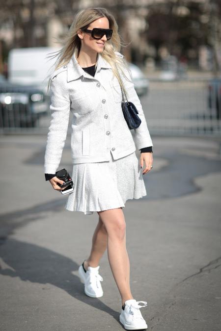 Девушка в юбке клеш, белая кофта на пуговицах, кроссовки
