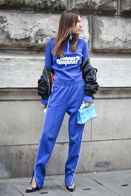 Модель одета в монохромном стиле с спортивном костюме василькового цвета