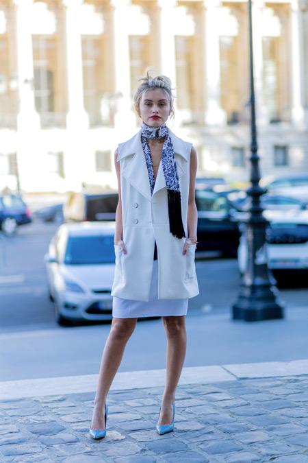 Модель в белой юбке карандаш, жакет без рукавов молочного цвета, шарфик и голубые туфли