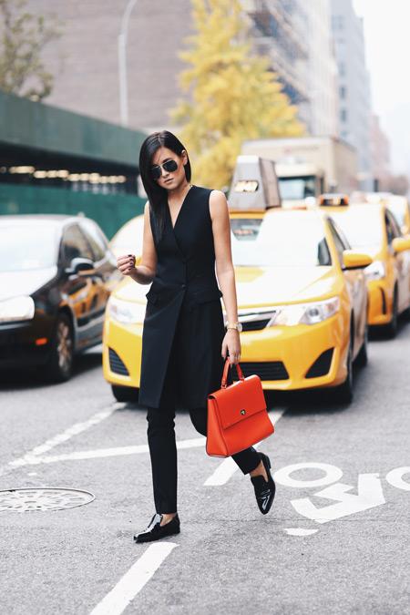 Модель в черных брюках, удлиненный кардиган без рукавов, оранжевая сумка