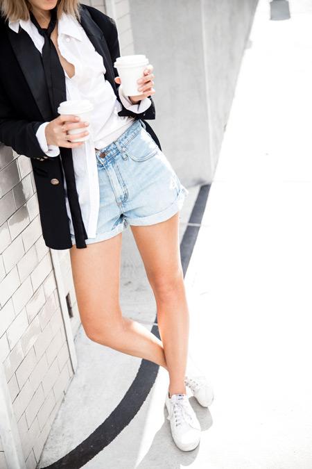 Модель в голубых шортах, белая рубашка и черный жакет