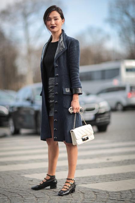 Модель в мини юбке, черной футболке и пальто, белая сумочка