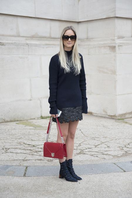 Модель в мини юбке и черной вязанной водолазке, красная сумочка и ботинки